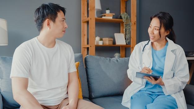 Jeune asie médecin professionnel de sexe féminin à l'aide de tablette numérique partageant de bonnes nouvelles de test de santé avec un patient masculin heureux s'asseoir sur le canapé dans la maison