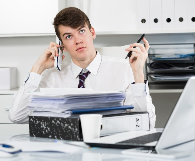 Jeune assistant parlant au téléphone