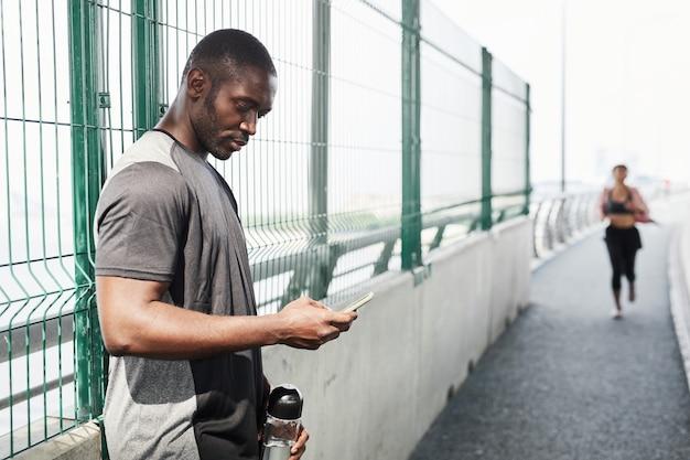 Jeune athlète africain avec une bouteille d'eau sms sur son téléphone portable après s'être entraîné à l'extérieur