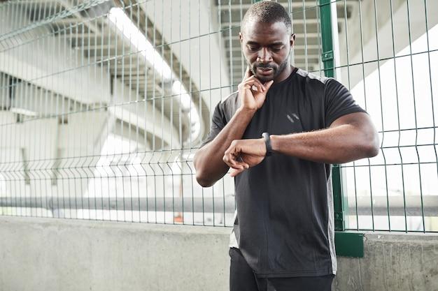 Jeune athlète africain regardant un bracelet de remise en forme et examinant son pouls après un entraînement sportif en salle de sport