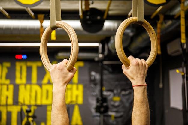 Jeune athlète avec des anneaux de gymnastique dans la salle de gym. concentrez-vous sur les bagues crossfit.