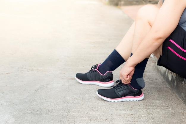 Jeune athlète asiatique femme attachant des chaussures de course