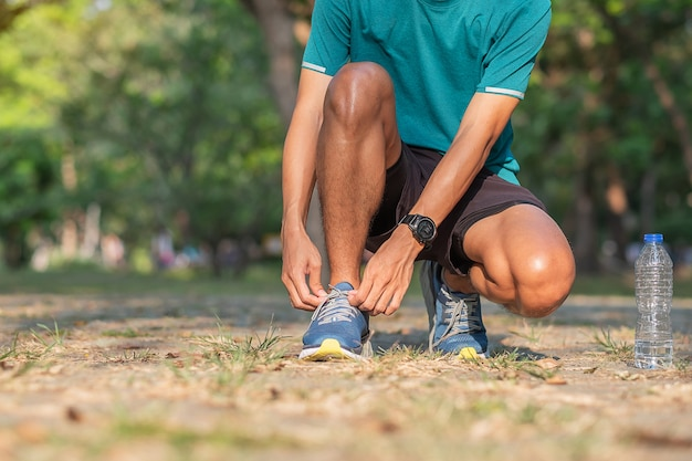 Jeune athlète attachant des chaussures de course dans le parc en plein air