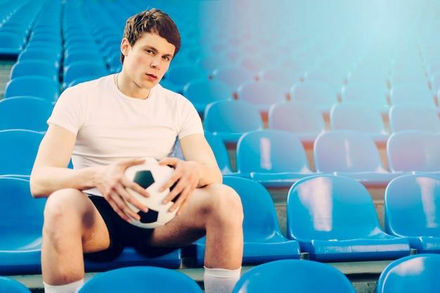 Jeune athlète avec ballon de football sur le stade