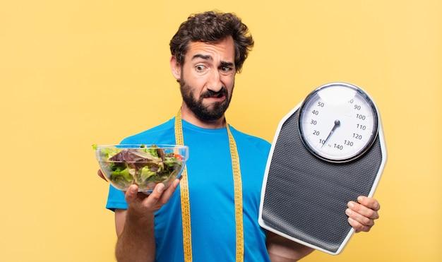 Jeune athlète barbu fou doutant ou incertain du concept d'expression et de régime et tenant une salade et ...