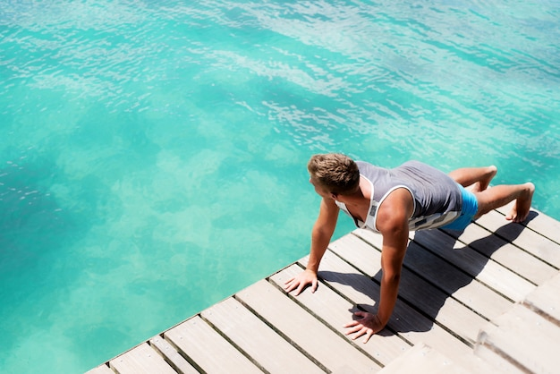 Jeune athlète bronzé faisant des pompes sur un quai de l'océan.