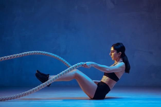 Jeune athlète caucasienne pratiquant sur bleu à la lumière du néon