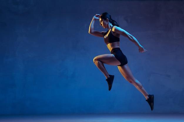 Jeune athlète caucasienne pratiquant sur fond bleu studio à la lumière du néon. gros plan d'un modèle sportif sautant haut, courant. musculation, mode de vie sain, concept de beauté et d'action.