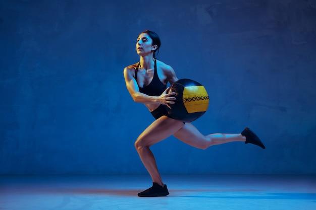 Jeune athlète caucasienne pratiquant sur fond bleu studio à la lumière du néon. modèle sportif faisant des fentes avec ballon, entraînement. musculation, mode de vie sain, concept de beauté et d'action.