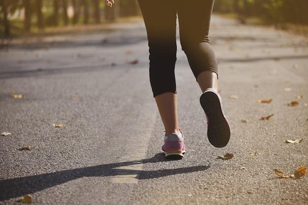Jeune athlète de coureur de femme de forme physique courant à la route