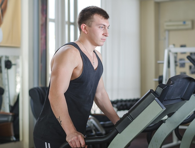 Jeune athlète en cours d'exécution à la salle de sport sur le tapis roulant