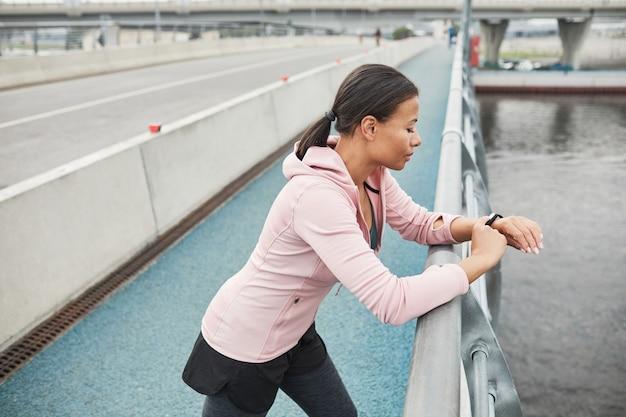 Jeune athlète debout sur le pont et examinant son pouls sur un bracelet de fitness pendant la course à pied...