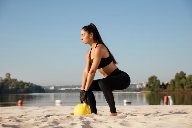 Jeune athlète féminine en bonne santé faisant de l'exercice à la plage