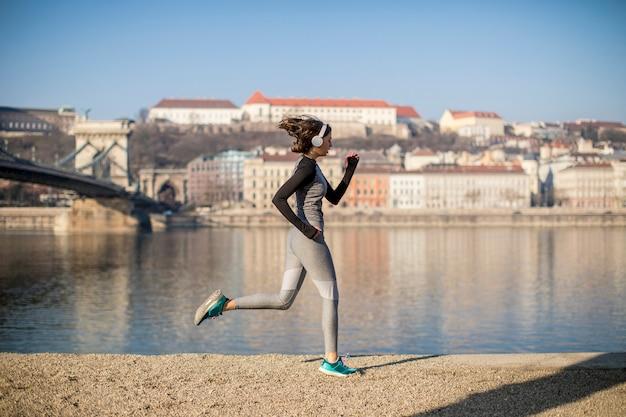 Jeune athlète féminine en cours d'exécution sur le front de mer à budapest, hongrie