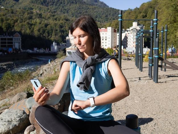 Une jeune athlète féminine est assise sur un terrain de sport en plein air,