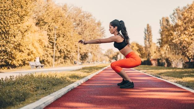 Jeune athlète féminine faisant des exercices de squat à l'extérieur dans le parc.