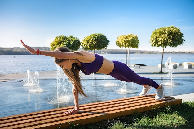 Jeune athlète féminine faisant des pompes à l'extérieur près du lac pendant la journée. mode de vie sain