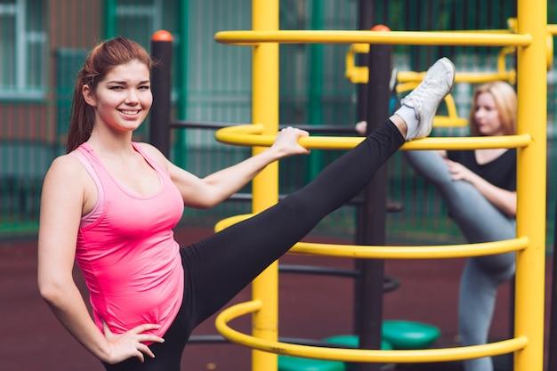 Une jeune athlète féminine de race blanche pratiquant des promenades en jambes sur la salle de sport pour des loisirs actifs en plein air. sports d'été et mode de vie sain.