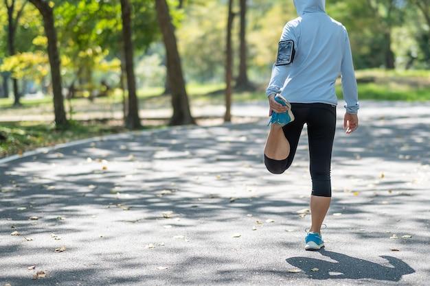 Jeune athlète femme qui s'étend dans le parc en plein air