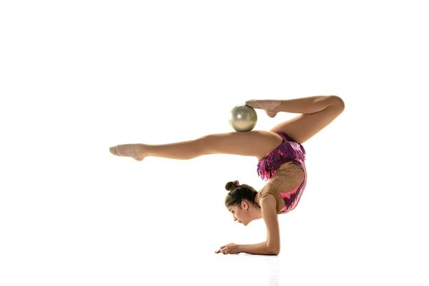 Jeune athlète de gymnastique isolé sur le mur blanc du studio