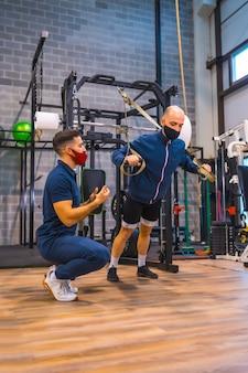 Un jeune athlète avec un instructeur dans la salle de sport faisant des exercices avec des bandelettes dans la pandémie de coronavirus