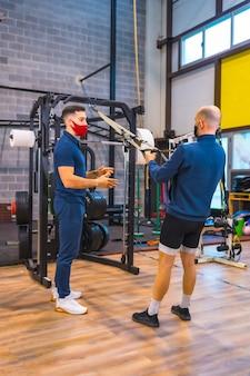 Un jeune athlète avec un instructeur dans la salle de sport faisant des exercices de bras dans la pandémie de coronavirus