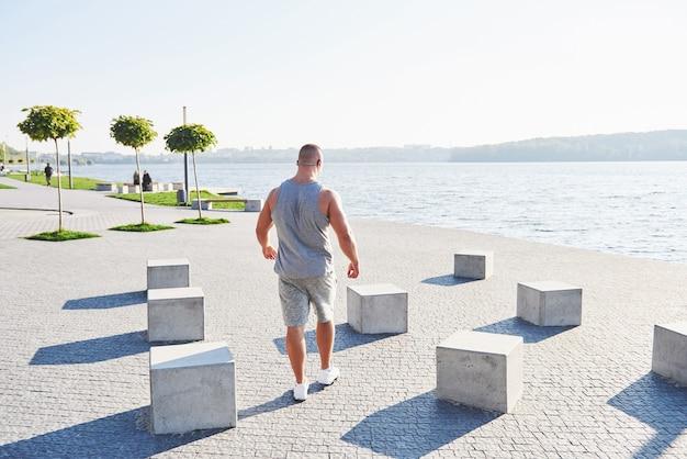 Jeune athlète masculin jogger s'entraînant et s'entraînant à l'extérieur en ville.