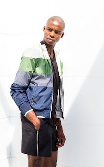 Jeune athlète masculin avec les mains dans sa poche, debout contre le mur blanc