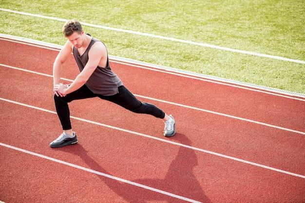 Jeune athlète masculin qui s'étend de son corps sur la piste de course