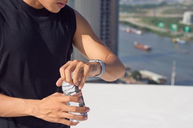 Jeune athlète masculin vérifiant la smartwatch, vue sur l'épaule