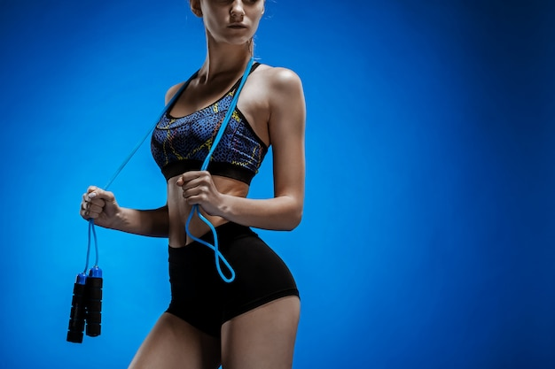 Jeune athlète musclé avec une corde à sauter sur bleu