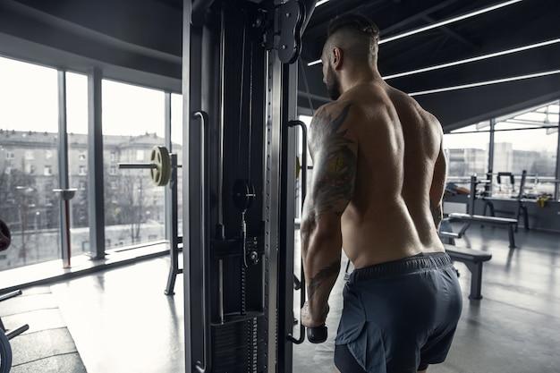 Jeune athlète musclé pratiquant dans une salle de sport avec les poids
