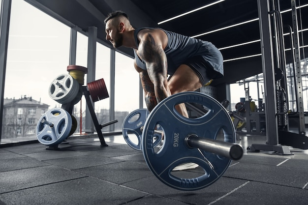 Jeune athlète musclé pratiquant des tractions dans une salle de sport avec haltères