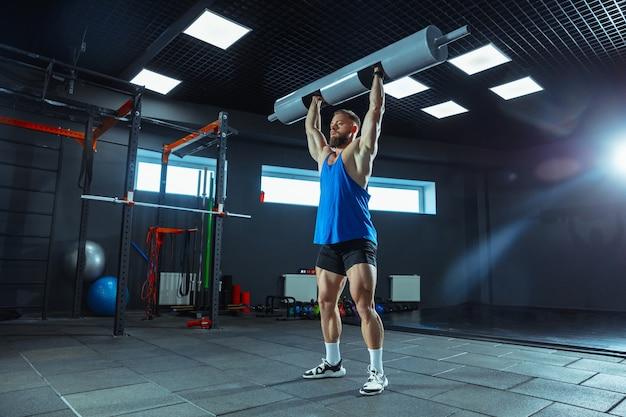 Jeune athlète musclé s'entraînant dans une salle de sport, faisant des exercices de force