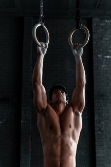 Jeune athlète musclé torse nu étirant ses bras dans des anneaux de gymnastique