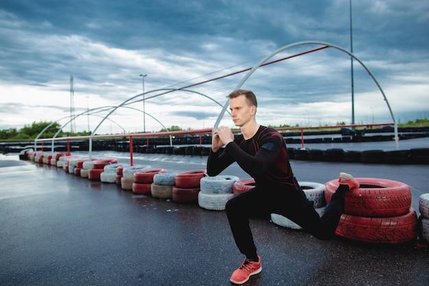 Un jeune athlète sérieux fait des fentes à l'extérieur. l'homme se réchauffe avant de faire du jogging le matin. le gars fait les exercices en jetant un pied sur le pneu. entraînement extérieur