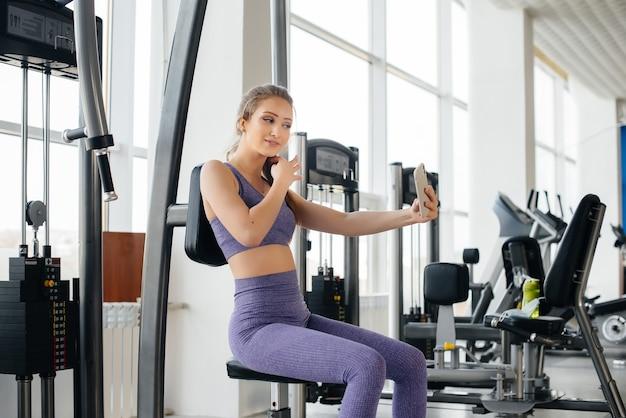 Une jeune athlète utilise son téléphone dans la salle de sport et prend un selfie.