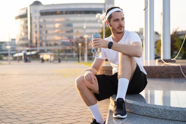 Jeune athlète en windrunner assis dans la rue après une bonne séance de jogging au coucher du soleil