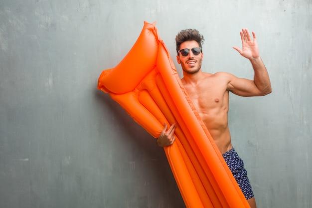 Jeune, athlétique, homme, porter, a, maillot de bain, contre, a, mur grunge, crier heureux