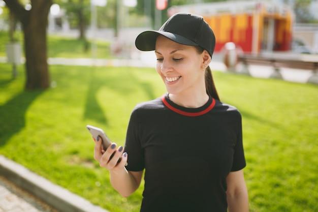Jeune athlétique souriante belle fille brune en uniforme noir et casquette utilisant un téléphone portable pendant l'entraînement, regardant sur un smartphone, debout dans le parc de la ville à l'extérieur