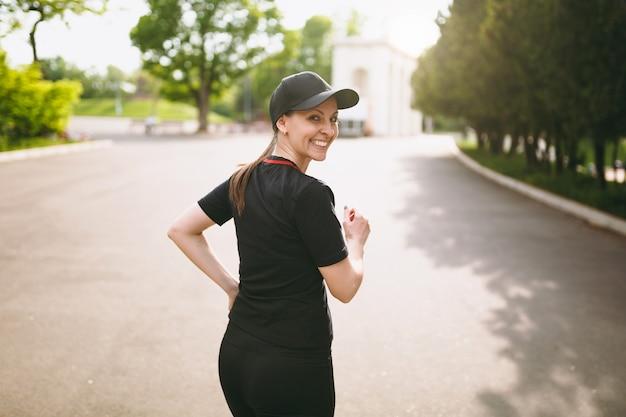 Jeune athlétique souriante belle fille brune en uniforme noir et entraînement à la casquette, faisant des exercices de sport et courant, regardant en arrière sur le chemin dans le parc de la ville à l'extérieur
