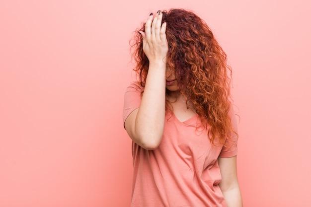 Jeune et authentique femme rousse oubliant quelque chose, claquant le front avec la paume et fermant les yeux