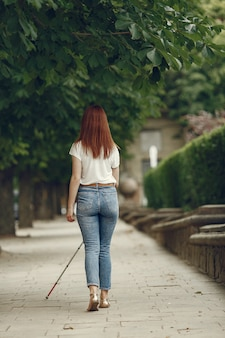 Jeune aveugle avec une longue canne marchant dans une ville