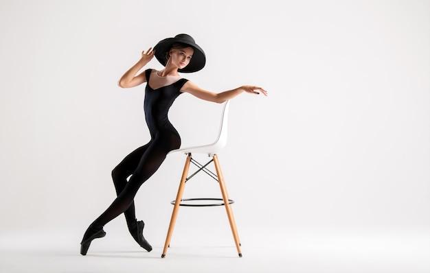 Jeune ballerine en chaussons de pointe noirs et chapeau élégant posant assis sur une chaise isolé sur fond blanc