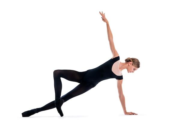 Jeune ballerine en chaussons de pointe noirs et justaucorps posant dans une pose gracieuse, isolé sur fond blanc