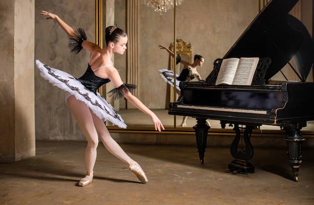 Jeune ballerine dans un tutu blanc dansant sur un beau vieux piano dans un intérieur vintage