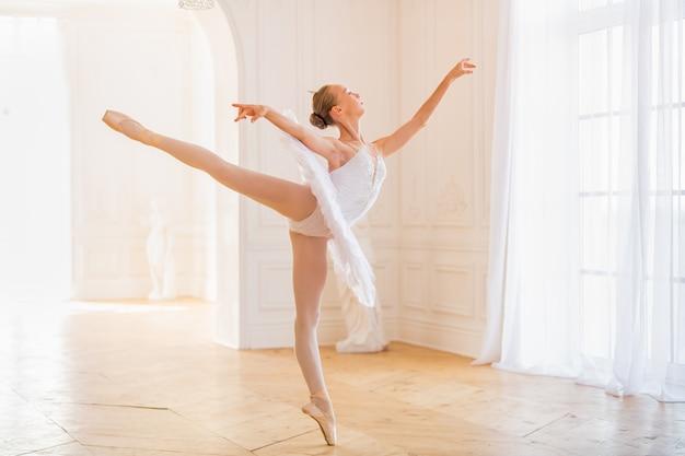 Jeune ballerine élancée dans un tutu blanc en chaussons de pointe danse dans une grande et belle salle blanche.