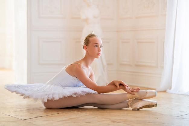 Jeune ballerine élancée dans un tutu blanc en chaussons de pointe est assise dans une pose gracieuse sur le sol dans une grande et belle salle blanche.