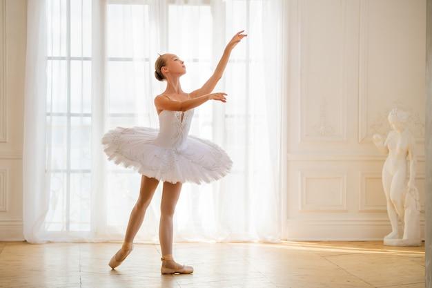 Jeune ballerine élancée dans un tutu blanc se dresse dans une arabesque sur des pointes dans une belle pièce blanche en face de la fenêtre.