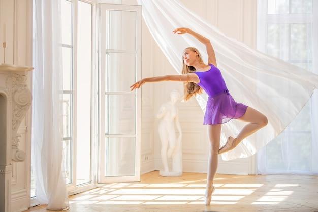 Jeune ballerine élancée en justaucorps lilas se dresse sur des pointes dans une belle pièce blanche près d'une fenêtre de carte postale, la brise agite le rideau.